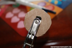 Use a hole punch to punch holes in the middle of the cardboard circle.