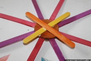 Glue 2 sticks in a X pattern over the top of the circle.