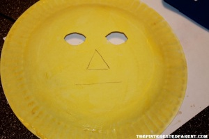 Draw your scarecrow face on the backside of the paper plate. Cut out the eyes. Paint your plate yellow.