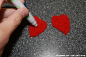 To form a strawberry, cut out two heart shapes. Dot the heart shapes with a green marker to add seeds.