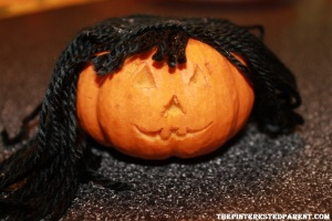 For mommy pumpkin, I just hot glued some yarn to the top of the pumpkin. I did the same for the baby & then braid the hair into pigtails